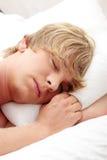 Homem que dorme em sua cama Fotografia de Stock