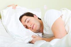 Homem que dorme na cama Imagem de Stock