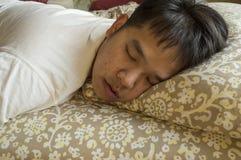 Homem que dorme na cama Imagens de Stock