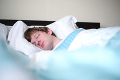 Homem que dorme na cama em casa Fotos de Stock