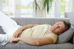 Homem que dorme no sofá Fotos de Stock