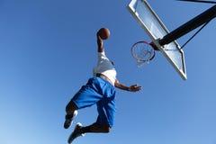 Homem que Dunking um basquetebol foto de stock