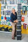 Homem que empilha caixas de ferramentas na loja de ferragens Fotografia de Stock Royalty Free