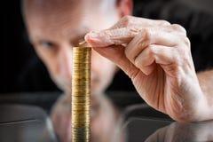 Homem que empilha moedas em uma tabela Fotografia de Stock Royalty Free