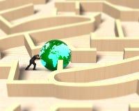 Homem que empurra o globo no jogo de madeira do labirinto Imagens de Stock