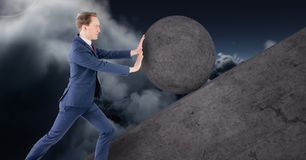 Homem que empurra o rolamento em volta da rocha imagem de stock royalty free