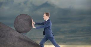 Homem que empurra o rolamento em volta da rocha fotos de stock royalty free
