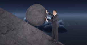 Homem que empurra o rolamento em volta da rocha foto de stock royalty free