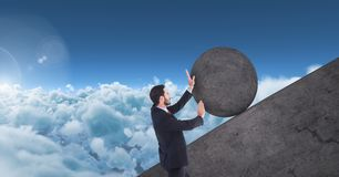 Homem que empurra o rolamento em volta da rocha imagem de stock