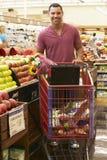 Homem que empurra o trole pelo contador do fruto no supermercado Imagem de Stock Royalty Free