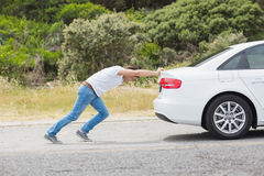 Homem que empurra seu carro Fotografia de Stock Royalty Free