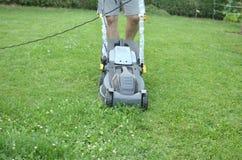Homem que empurra um cortador de grama Imagem de Stock Royalty Free