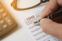 Homem que enche o formulário de imposto dos E.U. formulário de imposto nós mão do escritório da renda de negócio imagem de stock royalty free