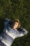 Homem que encontra-se em um gramado Imagens de Stock Royalty Free