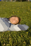 Homem que encontra-se em um gramado Fotografia de Stock