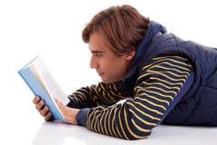 Homem que encontra-se lendo um livro imagens de stock royalty free