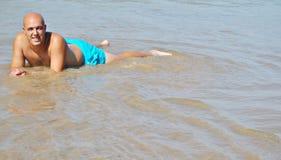 Homem que encontra-se na água foto de stock