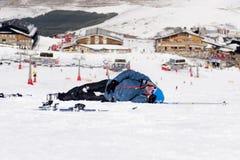 Homem que encontra-se na neve fria após o impacto do esqui no recurso de Sierra Nevada na Espanha com montanhas imagens de stock royalty free