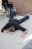 Homem que encontra-se no pavimento ao lado da cadeira de rodas Imagem de Stock Royalty Free