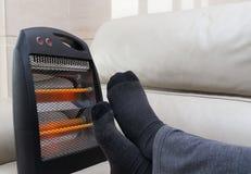 Homem que encontra-se no sofá com o calefator elétrico perto de seus pés imagem de stock royalty free