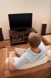 Homem que encontra-se no sofá que presta atenção à tevê Fotografia de Stock Royalty Free