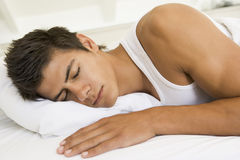 Homem que encontra-se no sono da cama Fotos de Stock Royalty Free