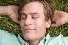 Homem que encontra-se no sono da grama Imagens de Stock Royalty Free