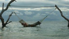 Homem que encontra-se sesta relaxado e feliz do sono na surpresa da rede do mar estabelecida em troncos de árvore na praia tropic vídeos de arquivo