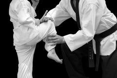 Homem que ensina a criança do lutador de Taekwondo Fotos de Stock Royalty Free