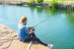 Homem que ensina sua amiga à pesca Conceito da data, do amor e do passatempo fotografia de stock