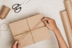 Homem que envolve o presente Um pacote envolvido no papel marrom e amarrado com Imagem de Stock Royalty Free
