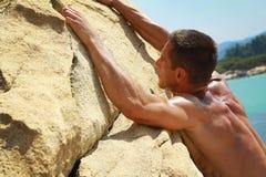 Homem que escala em rochas da montanha contra a água do mar Esportes extremos fora Férias de verão ativas Fotografia de Stock Royalty Free