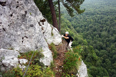 Homem que escala em uma rocha Imagens de Stock