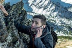 Homem que escala a montanha à parte superior e que fala no telefone Comunicações e realização do objetivo na carreira foto de stock royalty free