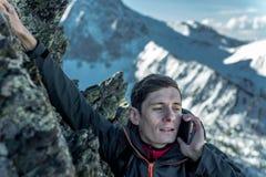 Homem que escala a montanha à parte superior e que fala no telefone Comunicações e realização do objetivo na carreira imagens de stock