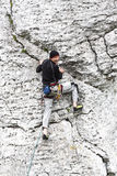 Homem que escala a parede rochosa natural Fotos de Stock