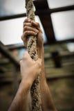 Homem que escala uma corda durante o curso de obstáculo imagens de stock