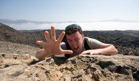 Homem que escala uma montanha Foto de Stock Royalty Free
