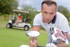 Homem que escolhe o clube de golfe imagens de stock royalty free
