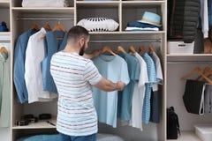 Homem que escolhe o equipamento do grande armário do vestuário com roupa e material da casa fotografia de stock