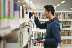 Homem que escolhe o livro na biblioteca Imagens de Stock