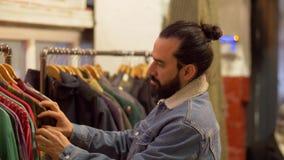 Homem que escolhe a roupa na loja de roupa do vintage filme