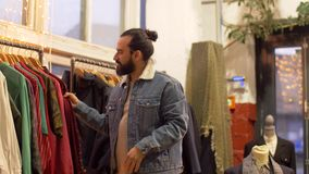 Homem que escolhe a roupa na loja de roupa do vintage vídeos de arquivo