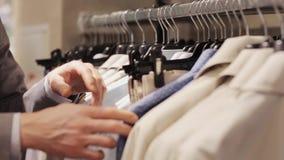 Homem que escolhe a roupa na loja de roupa video estoque