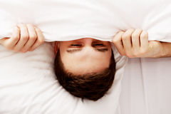 Homem que esconde na cama sob folhas Imagens de Stock Royalty Free