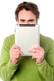 Homem que esconde sua cara com dispositivo da tabuleta Imagens de Stock