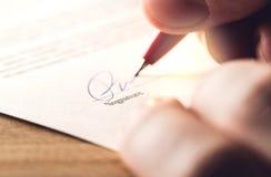 Homem que escreve a assinatura com a pena no papel imagem de stock royalty free