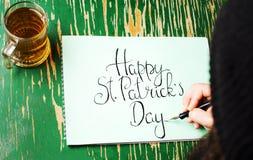 Homem que escreve um cartão feliz do dia de St Patrick Fotografia de Stock Royalty Free