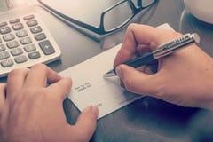 Homem que escreve um cheque do pagamento Imagem de Stock Royalty Free