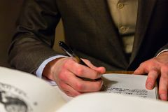 Homem que escreve uma letra em um jornal imagem de stock royalty free